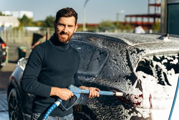 Mezzo busto ritratto dell'uomo che tiene in mano uno spruzzatore d'acqua ad alta pressione per il lavaggio dell'auto. concetto di disinfezione e pulizia antisettica del veicolo
