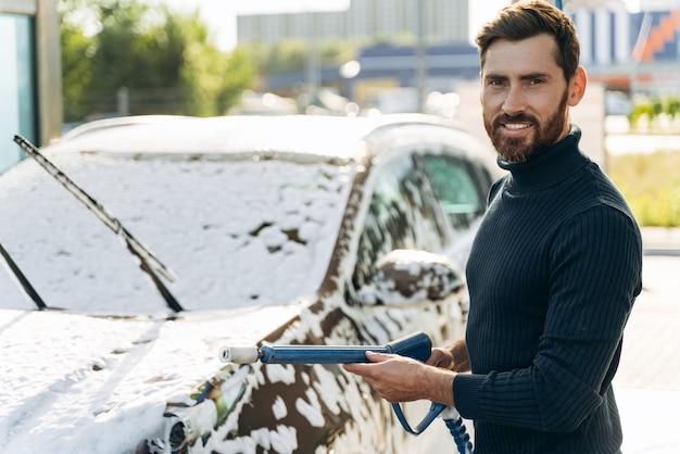 Ritratto in vita dell'uomo che sorride alla telecamera mentre tiene in mano uno spruzzatore d'acqua ad alta pressione per il lavaggio dell'auto. concetto di disinfezione e pulizia antisettica del veicolo