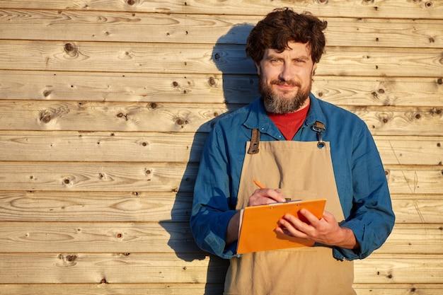 Mezzo busto ritratto di uomo barbuto maturo tenendo appunti e indossando il grembiule mentre si sta in piedi contro la superficie in legno rustico alla luce del sole, copia dello spazio