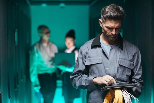 Ritratto in vita di un ingegnere di rete maturo che utilizza un tablet digitale nella sala server durante i lavori di manutenzione nel data center, spazio di copia