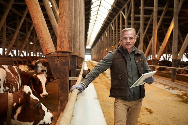 Vita ritratto dell'uomo maturo moderno che tiene appunti e sorride alla macchina fotografica mentre ispeziona il bestiame al capannone nel caseificio, spazio di copia