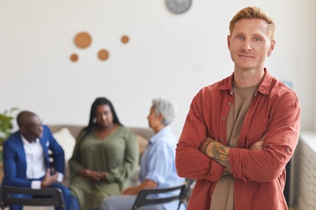 Mezzo busto ritratto dell'uomo moderno tatuato in posa con sicurezza e con persone sedute in cerchio in superficie, concetto di gruppo di supporto, copia dello spazio
