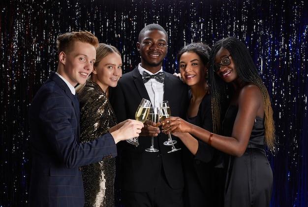 Mezzo busto ritratto di gruppo multietnico di amici tintinnanti bicchieri di champagne e sorridere alla telecamera mentre si gode di una festa elegante
