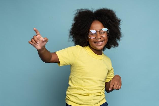 Mezzo busto di una ragazza adolescente energica positiva con i capelli castani con una maglietta gialla brillante che balla e si sente benissimo. concetto di attività di hobby. foto in studio, sfondo blu