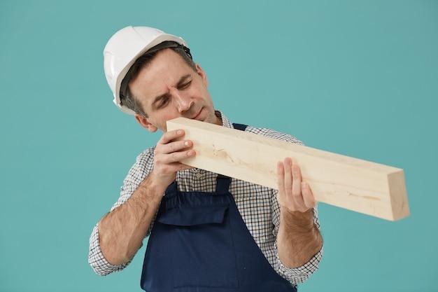 Mezzo busto ritratto di lavoratore professionista in possesso di legno