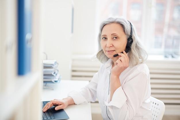 Mezzo busto ritratto di senior imprenditrice parlando al microfono e guardando mentre si lavora con il computer portatile in ufficio interno