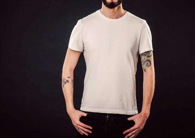 Mezzo busto ritratto di serio uomo attraente elegante con folta barba guarda con sicurezza, vestito con una maglietta bianca casual