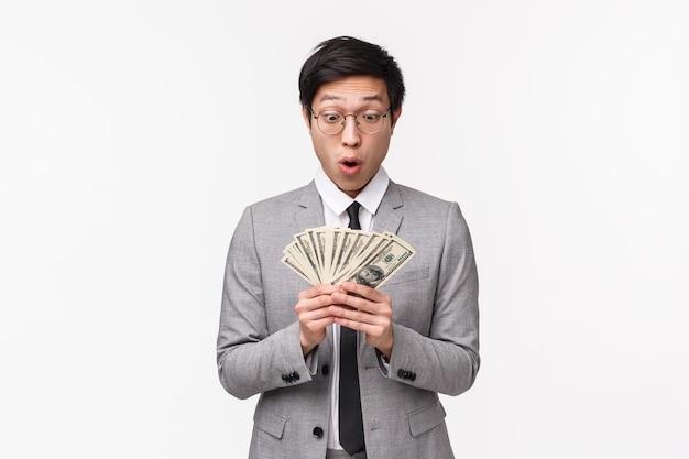 Ritratto in vita di scioccato e stupito, giovane manager asiatico sorpreso ha trovato un caso con migliaia di dollari, guardando contanti con stupore e tremato, ansimando elettrizzato, su un muro bianco