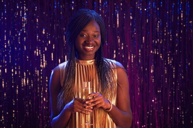 Mezzo busto ritratto di sorridente ragazza afro-americana tenendo il bicchiere di champagne e guardando la fotocamera mentre in piedi su sfondo scintillante alla festa, copia spazio