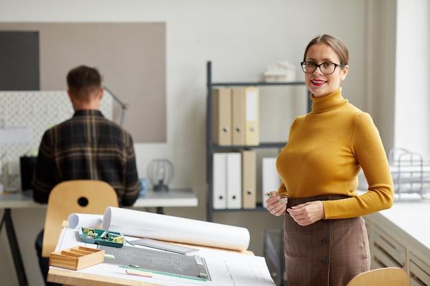 Mezzo busto ritratto di donna sorridente architetto stando in piedi dalla scrivania in ufficio,