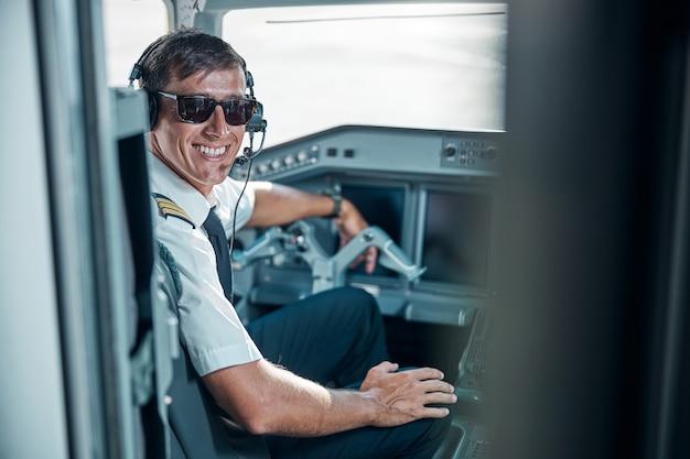 Ritratto in vita di un bel professionista maschio sorridente in uniforme e auricolari seduto al comando in cabina di pilotaggio