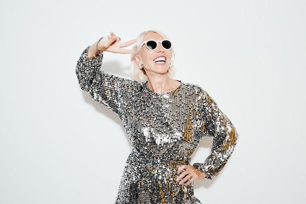 Ritratto in vita di una donna matura sorridente che indossa un abito glamour contro il muro bianco, girato con il flash