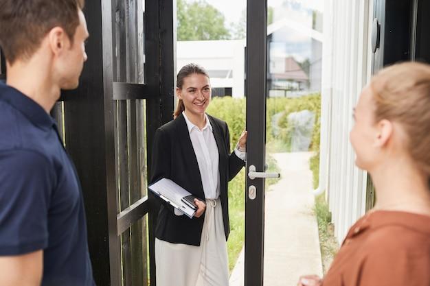 Mezzo busto ritratto di un agente immobiliare sorridente che incontra una giovane coppia in piedi sulla porta mentre acquista una nuova casa, copia spazio