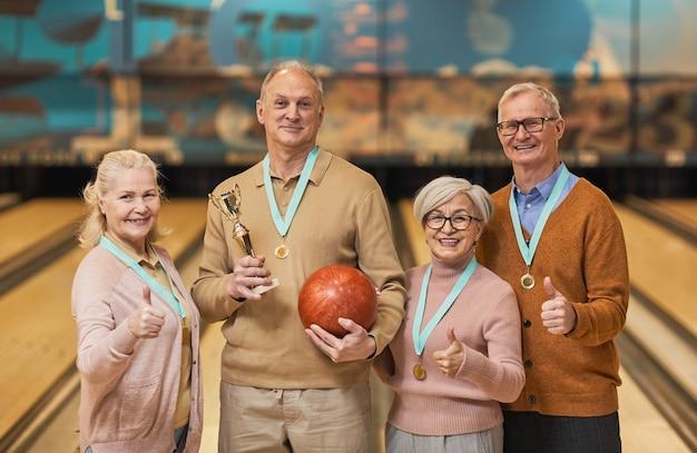 Mezzo busto ritratto di una squadra senior sorridente che indossa medaglie tenendo in mano il trofeo e guardando la telecamera mentre si trova in una pista da bowling dopo aver vinto la partita