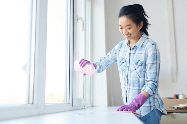 Mezzo busto ritratto di donna sorridente lavare i vetri durante le pulizie di primavera, concentrarsi sulle mani femminili che indossano guanti rosa