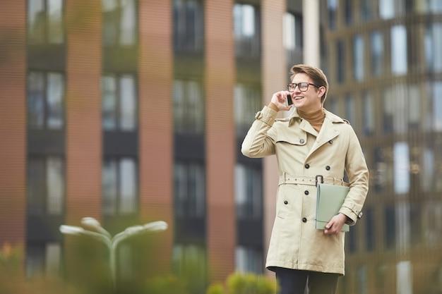Mezzo busto ritratto di giovane uomo d'affari sorridente che parla da smartphone all'aperto mentre si cammina verso la telecamera in ambiente urbano della città, copia dello spazio
