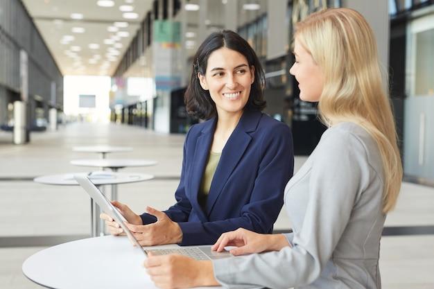 Vita ritratto di imprenditrice di successo a discutere di lavoro con il partner femminile mentre si sta in piedi alla scrivania in edificio per uffici,