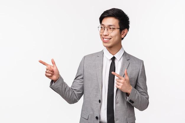 Ritratto di giovane uomo asiatico di successo, professionale che inizia la sua carriera in azienda it, presentando il suo progetto sulla riunione, guardando e indicando a sinistra con un sorriso fiducioso sul muro bianco