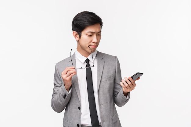 Vita-up ritratto di uomo d'affari asiatico bello riflessivo prendere una decisione, guardando il display del telefono cellulare come scegliere quale ordine di consegna online, fare la scelta dello shopping internet utilizzando l'app per smartphone