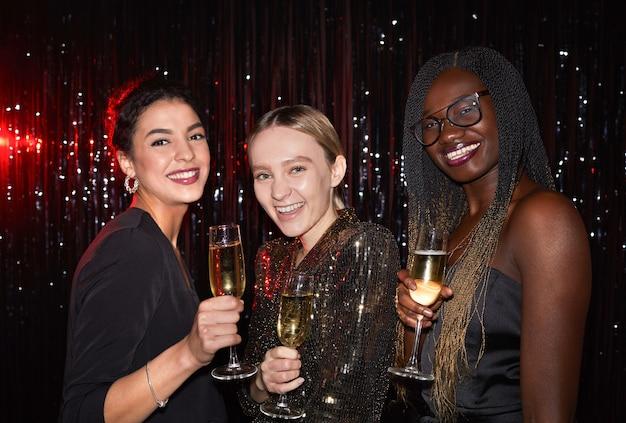 Mezzo busto ritratto di tre giovani donne eleganti che tengono bicchieri di champagne e sorridendo alla telecamera mentre posa su sfondo scintillante alla festa, girato con flash