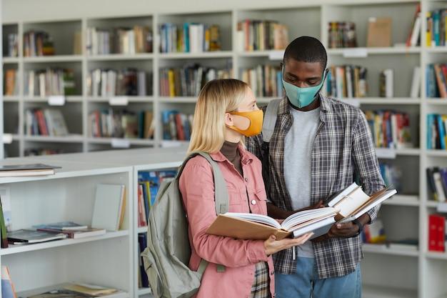 Mezzo busto ritratto di due studenti che indossano maschere in piedi nella biblioteca scolastica e con in mano libri,