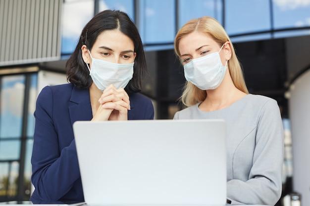 Mezzo busto ritratto di due imprenditrici di successo che indossano maschere mentre si guarda lo schermo del laptop in piedi alla scrivania in edificio per uffici