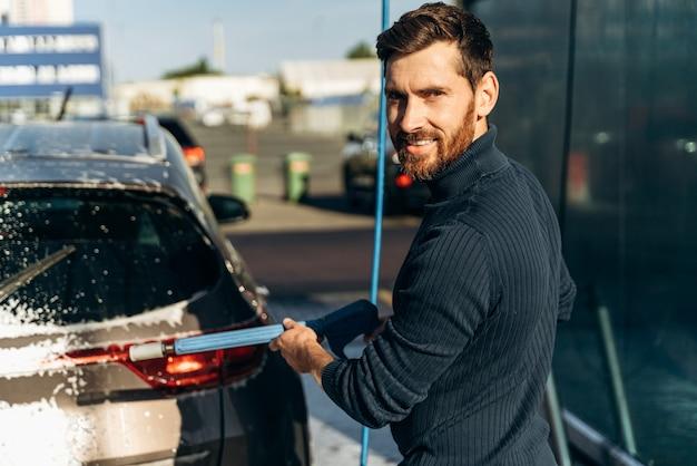 Mezzo busto verticale dell'uomo caucasico che tiene in mano un'attrezzatura speciale e sorride alla telecamera mentre pulisce l'auto con acqua ad alta pressione. concetto di lavaggio auto. messa a fuoco selettiva
