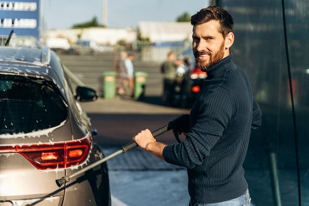 Mezzo busto verticale dell'uomo che lava la sua auto in strada usando un'idropulitrice con schiuma. piacere maschio che sorride alla telecamera