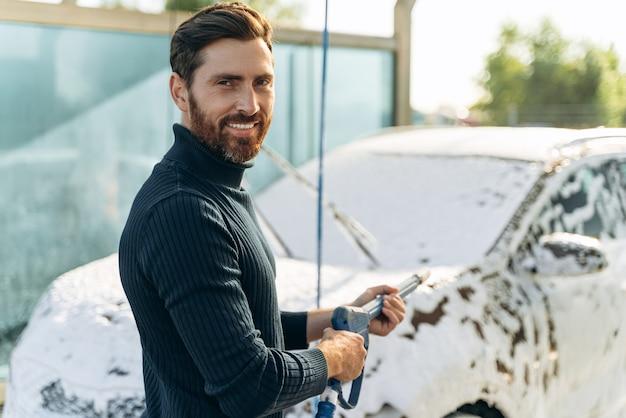 Vista verticale in vita dell'uomo del piacere che lava la sua auto in strada usando un'idropulitrice con schiuma mentre sorride alla telecamera