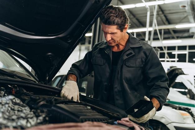 Mezzo busto verticale del meccanico di auto serio nel suo negozio di riparazioni in piedi accanto all'auto. primo piano del motore