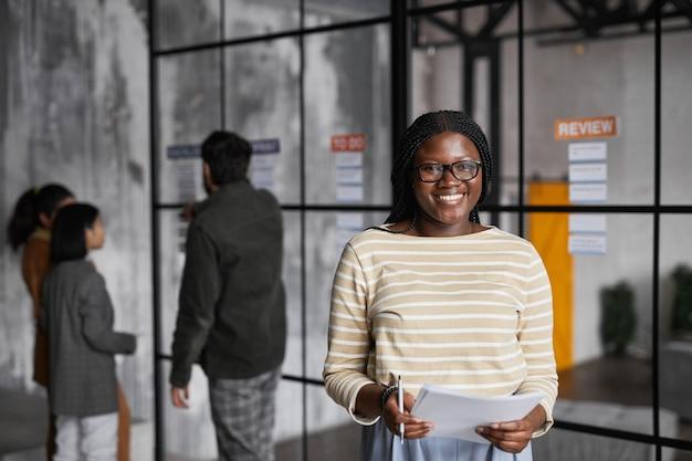 Ritratto in vita di una giovane donna d'affari afro-americana in piedi accanto a una parete di vetro mentre pianifica un progetto in un ufficio moderno, copia spazio