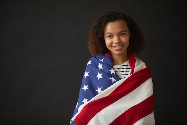 Mezzo busto ritratto di giovane ragazza afro-americana avvolta nella bandiera americana mentre posa
