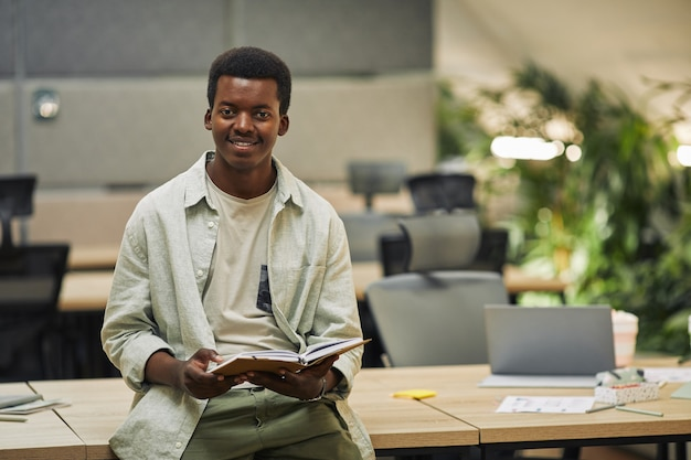 Mezzo busto ritratto di giovane afro-americano sorridente mentre in piedi azienda pianificatore e appoggiato sulla scrivania in ufficio moderno, copia spazio