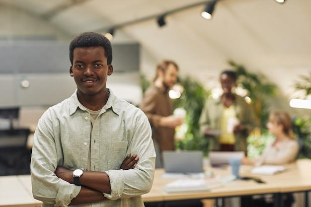 Mezzo busto ritratto di giovane afro-americano mentre posa con fiducia in piedi con le braccia incrociate in ufficio moderno con persone che lavorano in superficie, spazio di copia