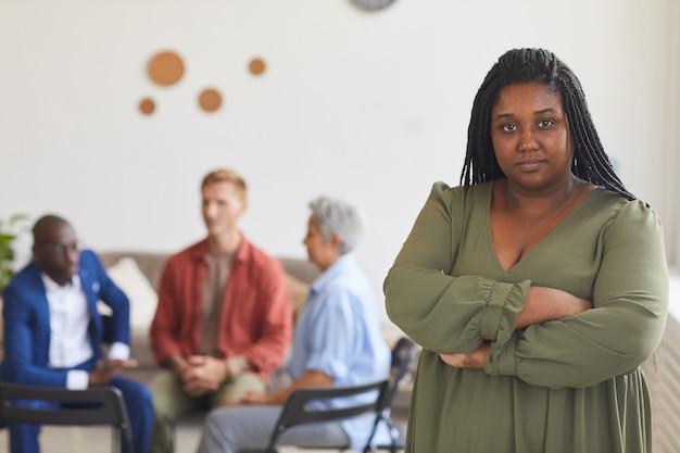 Mezzo busto ritratto di giovane donna afro-americana con persone sedute in cerchio in superficie, concetto di gruppo di sostegno, copia dello spazio