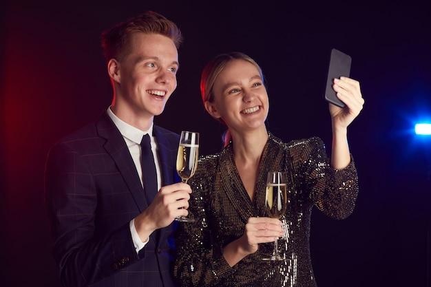 Mezzo busto ritratto di giovane coppia che cattura foto selfie tramite smartphone mentre vi godete la festa durante la notte del ballo, copia dello spazio
