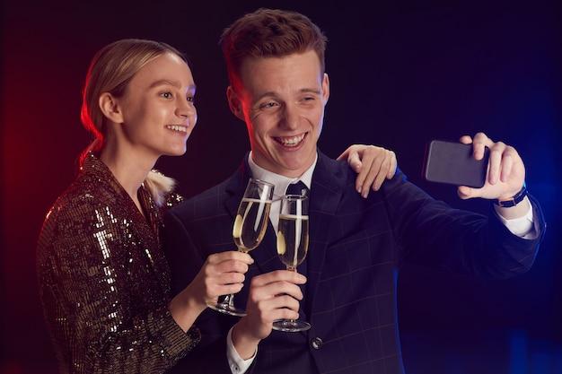 Mezzo busto ritratto di giovane coppia che cattura foto selfie tramite smartphone mentre vi godete la festa alla notte del ballo in piedi sullo sfondo di mancanza