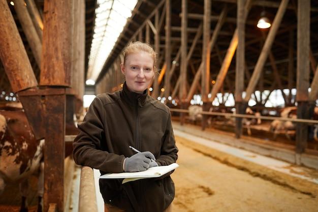 Vita ritratto di giovane lavoratore di sesso femminile che tiene appunti e sorride alla macchina fotografica mentre ispeziona il bestiame al capannone nel caseificio, spazio di copia