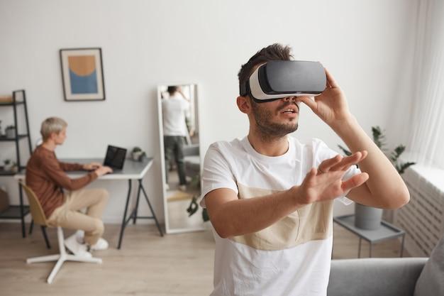 Ritratto in vita di un giovane che usa la realtà virtuale e allunga la mano nell'interno della casa, copia spazio