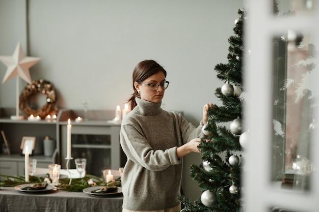 Mezzo busto ritratto di giovane donna che appende ornamenti sull'albero di natale a casa in elegante argento e g...