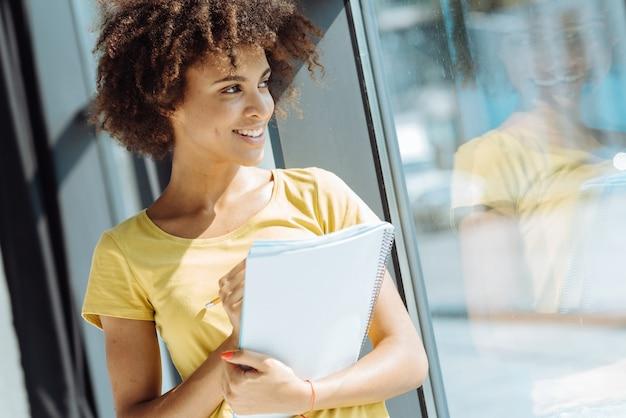 Mezzo busto di studente afroamericano femminile riccio positivo che tiene il suo taccuino e che sorride mentre levandosi in piedi vicino alla finestra