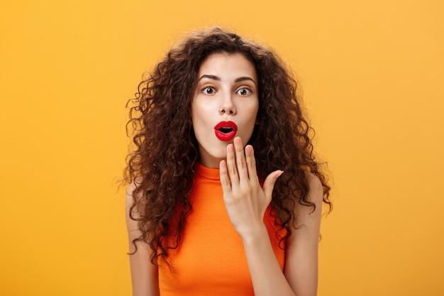 Colpo in vita di una donna caucasica stupita ed eccitata con i capelli ricci in bocca rossa di apertura del rossetto dalla sorpresa che lo copre con il palmo che ascolta voci scioccanti che reagiscono stupiti a notizie divertenti.