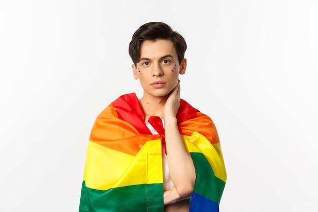 Mezzo busto di bellissimo uomo gay con glitter sul viso, avvolgersi con la bandiera arcobaleno lgbt e toccare delicatamente il viso, guardando la telecamera, bianco