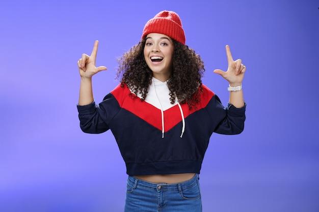 Mezzo busto di allegra giovane donna energizzata che chiama un amico invitando a uscire mentre il tempo è fantastico rivolto verso l'alto con le mani alzate sorridenti che posano ampiamente in cappello invernale rosso su sfondo blu.