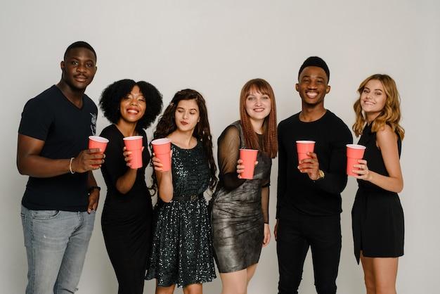 Mezzo busto di sei amici che si divertono e bevono alcolici durante la festa di capodanno