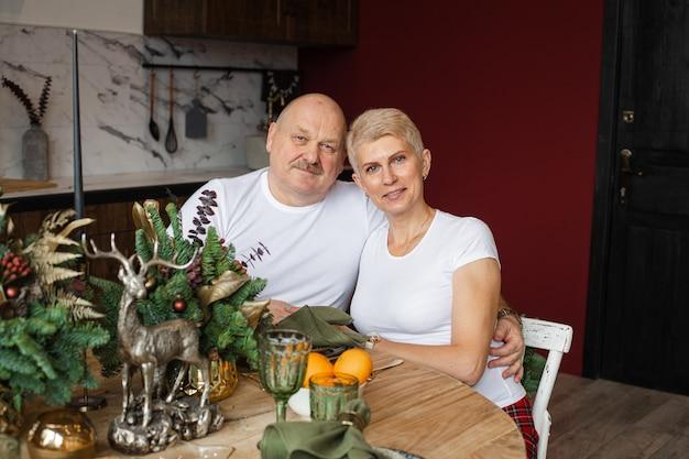Mezzo busto di sorridente uomo e donna che celebrano il natale nella loro casa