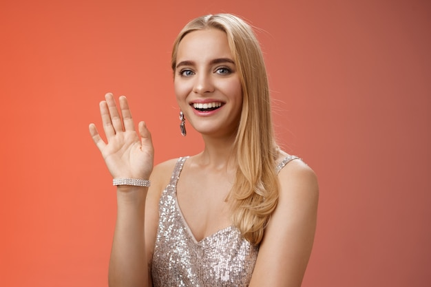 Girovita girato in studio amichevole attraente elegante donna bionda tenera dire ciao agitando la mano alzata saluto accogliente amico sorridente felice presentandosi ciao gesto, sfondo rosso.