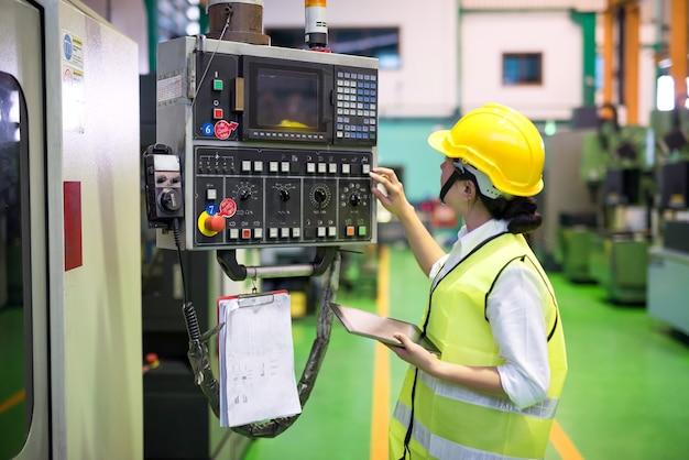 Tecnico in vita lavoratrice con macchine a microchip a transistor di comando tablet sul pannello di controllo