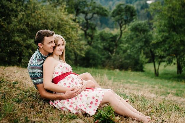 Aspetta piccola. famiglia felice. donna incinta con l'amato marito seduto sull'erba, ammirando il paesaggio. pancia rotonda. il momento tenero sincero. sfondo, natura, parco, albero, foresta, nove mesi di felicità