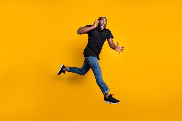 Aspetta, presto! foto laterale di profilo completo del corpo del ragazzo afroamericano divertente pazzo che salta parlare con il cellulare corri acquista sconti venerdì nero indossa t-shirt denim jeans isolato muro di colore giallo